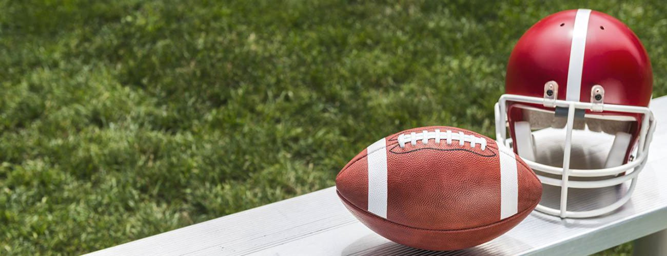 a football and helmet on the sidelines of a football field