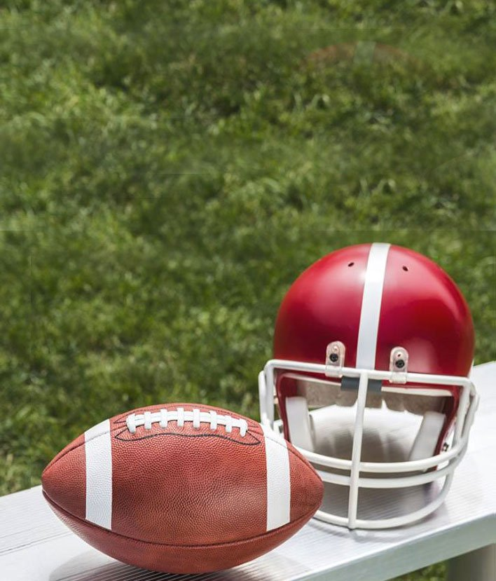 a red football helmet and football sit on a bench near a football field